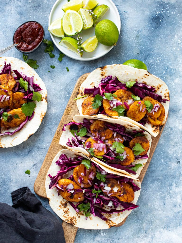 plantain tacos on a chopping board with limes
